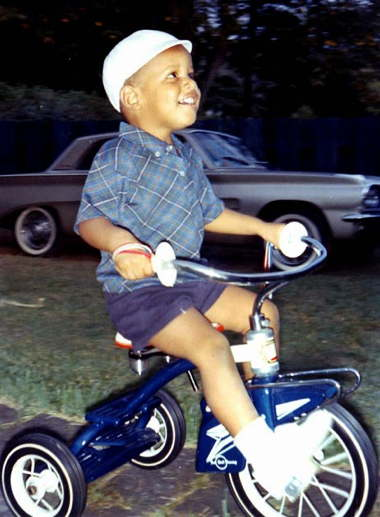 a_young_barack_obama_riding_a_tricycle.jpg